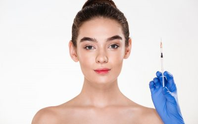 Image of pretty woman preparing for beauty injection made by doctor in latex gloves, holding syringe with hyaluronic acid over white background