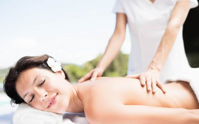 Woman receiving a back massage from masseur in a spa